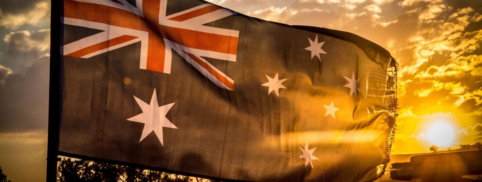Sunset shining through Australian flags and national emblems of Australia