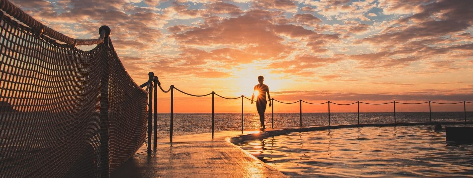 Man walking along edge of ocean pool at sunset at Sydney's Top Instagram Spots