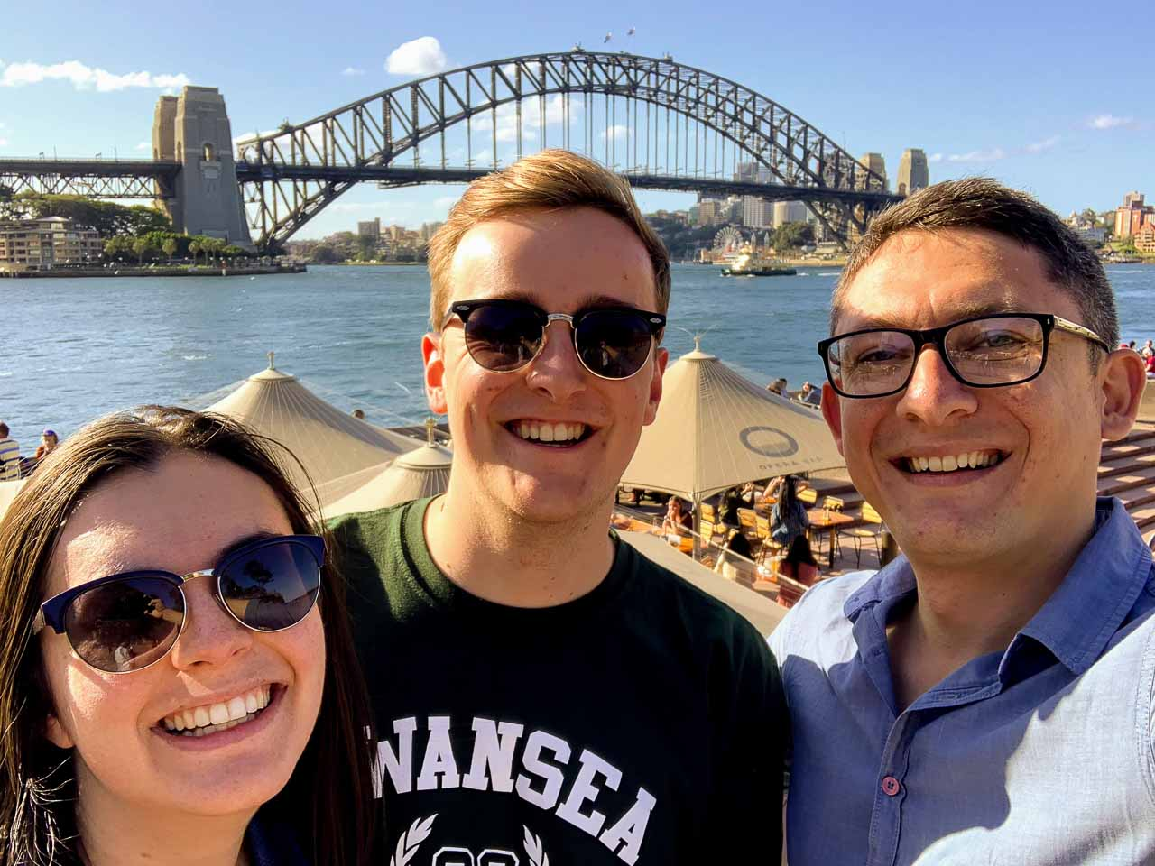 Tour guide, man & woman overlooking restaurant, Sydney Harbour & Harbour Bridge background