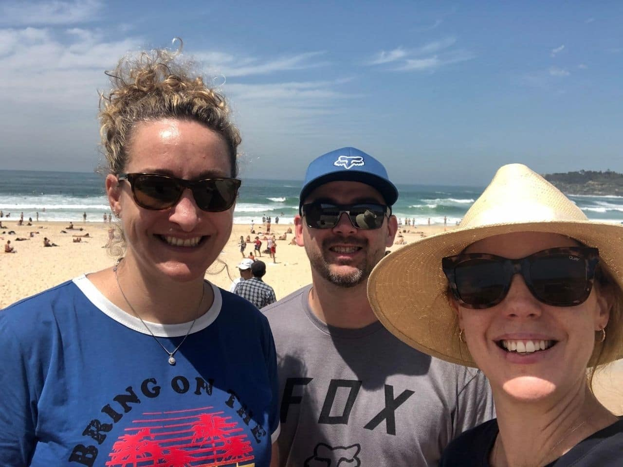 Tour guide and couple taking selfie at Bondi Beach wearing hats standing in front of ocean